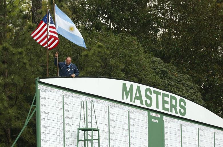 Apr 3, 2017; Augusta, GA, USA; An Augusta National employee removes flags from the scoreboard at the first hole as a second weather warning and a tornado watch suspends play for the day during a practice round at The Masters at Augusta National GC. The suspension forced patrons to evacuate the course. Mandatory Credit: Rob Schumacher-USA TODAY Sports