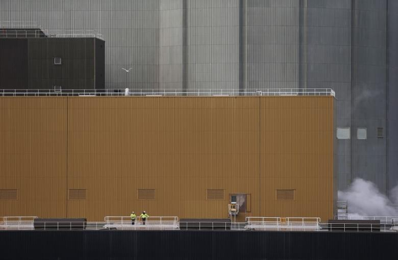 FILE PHOTO: Workers stand outside Wylfa nuclear power station in Cemaes, northern Wales  February 22, 2013.  REUTERS/Suzanne Plunkett