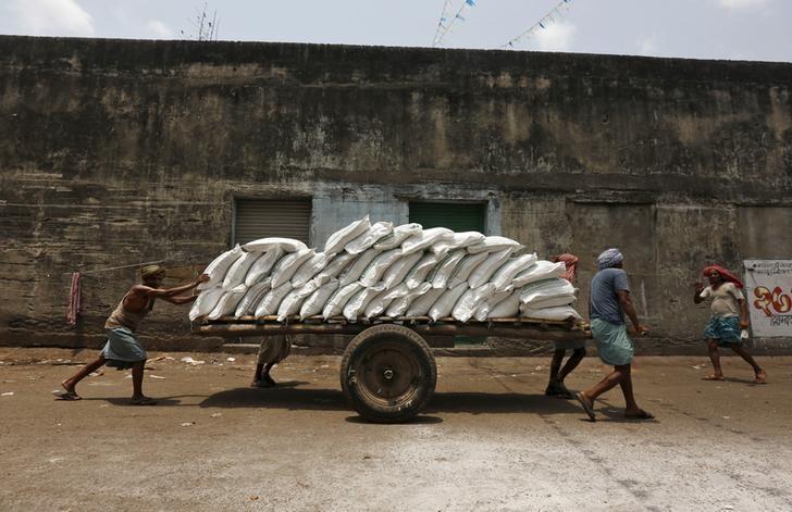 Labourers push a handcart loaded with sacks of sugar at a wholesale market in Kolkata, India, April 26, 2016. REUTERS/Rupak De Chowdhuri/Files