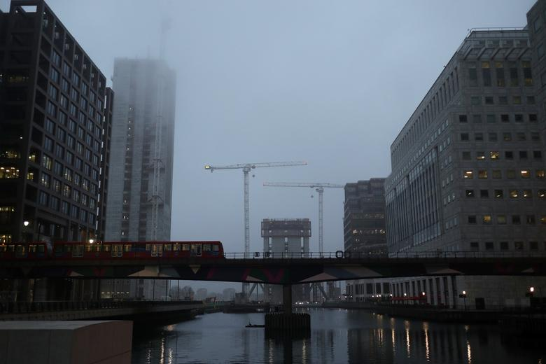 A DLR train crosses a bridge in front of construction work in early morning mist in London's Canary Wharf financial district, Britain March 28, 2017. REUTERS/Russell Boyce