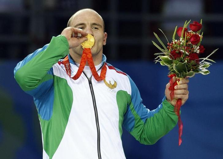 Artur Taymazov of Uzbekistan poses with his gold medal in the 120kg men's freestyle wrestling at the Beijing 2008 Olympic Games August 21, 2008. REUTERS/Oleg Popov/Files