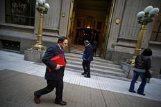 Peatones caminan frente a la entrada principal del Banco Central de Chile en el centro de Santiago, Chile. 25 de agosto 2014. La actividad económica en Chile se contrajo un 1,3 por ciento en febrero, su peor desempeño desde la crisis global del 2009, debido a los efectos de una extensa huelga minera y voraces incendios forestales, lo que allanaría el camino para un mayor estímulo monetario. REUTERS/Ivan Alvarado (CHILE - Tags: BUSINESS) - RTR43Q2O