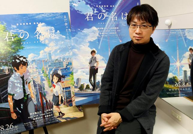 FILE PHOTO - Japanese anime director Makoto Shinkai poses for a photo in front of posters of his animated film 'Your Name' after an interview with Reuters in Tokyo, Japan, November 16, 2016. REUTERS/Toru Hanai/File Photo