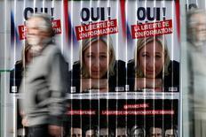 IMAGEN DE ARCHIVO: Un hombre camina frente a un poster de la candidate presidencial francesa Marine Le Pen, en Paris, Francia.  5 de abril 2017. El euro probablemente baje alrededor de un 5 por ciento a mínimos en 15 años y se acerque a la paridad frente al dólar inmediatamente después de un potencial triunfo de Marine Le Pen en las elecciones presidenciales francesas de mayo, de acuerdo con estrategas cambiarios encuestados por Reuters. REUTERS/Gonzalo Fuentes/File Photo