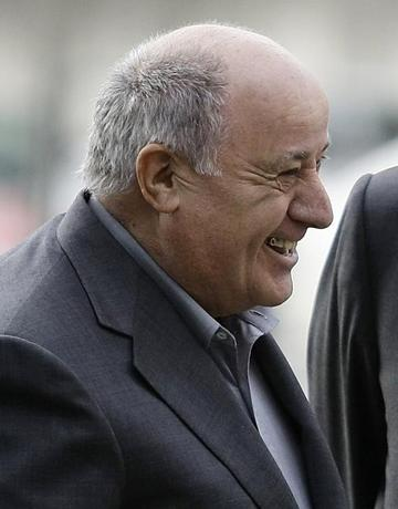 Amancio Ortega, chairman of Spanish global fashion group Inditex, laughs during a visit of Spain's Princess Letizia and Crown Prince Felipe to his factory in Coruna, northern Spain December 2, 2008. REUTERS/Miguel Vidal/Files