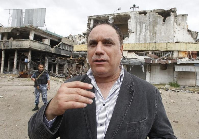 FILE PHOTO: Homs provincial governor Talal Barazi gestures as he walks in old Homs city May 8, 2014.  REUTERS/Khaled al-Hariri