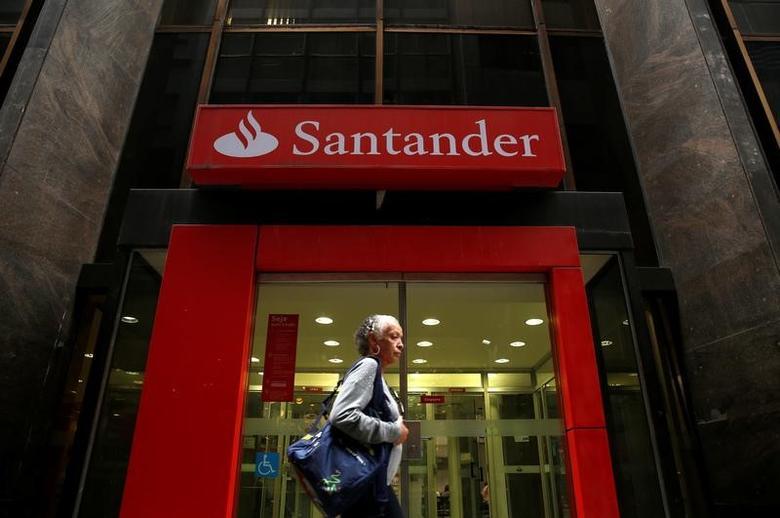 A woman walks past a Banco Santander branch in downtown Rio de Janeiro August 19, 2014.   REUTERS/Pilar Olivares/File Photo