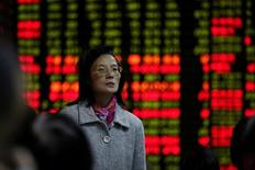 Una inversora observa una pantalla electrónica que muestra información de acciones en una casa de valores en Shanghái, China, 9 de noviembre del 2016.Las acciones chinas subieron el viernes para anotar su mejor semana desde fines de noviembre, lideradas por el cierre del referencial de Shanghái en un máximo de 15 meses, luego de que el apetito por el riesgo fue reforzado por la decisión de Pekín de lanzar una nueva zona económica en la provincia de Hebei. REUTERS/Aly Song