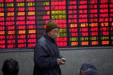 Un investigador camina frente una tabla electrónica que muestra información sobre la bolsa en Shanghái, China. 3 de enero 2017. Las acciones chinas cayeron el lunes luego de que el regulador de valores del país buscó enfriar la fiebre especulativa en torno a los planes para establecer una nueva zona económica en el país. REUTERS/Aly Song - RTX2XBA6