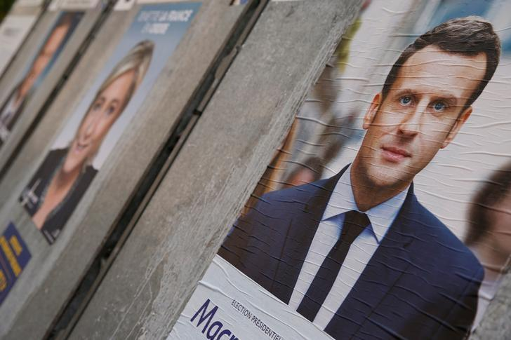 People walk past campaign posters of Emmanuel Macron (L), head of the political movement En Marche! (Onwards!), and Marine Le Pen (R), French National Front (FN) political party leader, two of the eleven candidates who run in the 2017 French presidential election, are seen in Paris, France, April 10, 2017. REUTERS/Gonzalo Fuentes