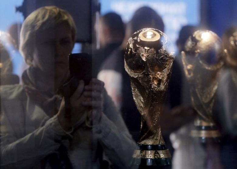 A woman is seen through the glass while taking pictures of the World Cup trophy, which is on display during a ceremony marking 1,000 days until the beginning of the 2018 FIFA World Cup in central Moscow, Russia, September 18, 2015. REUTERS/Maxim Shemetov