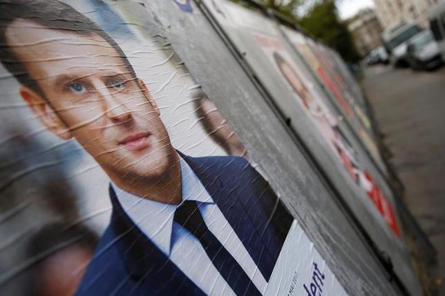 4月10日、フランス大統領選の最有力候補とされるマクロン前経済相は、グーグルやフェイスブックなどの米インターネット大手にメッセージサービスで暗号化された通信内容を当局に提供するよう求めていく考えを示した。写真はマクロン氏の選挙ポスター。パリで撮影(2017年 ロイター/Gonzalo Fuentes)