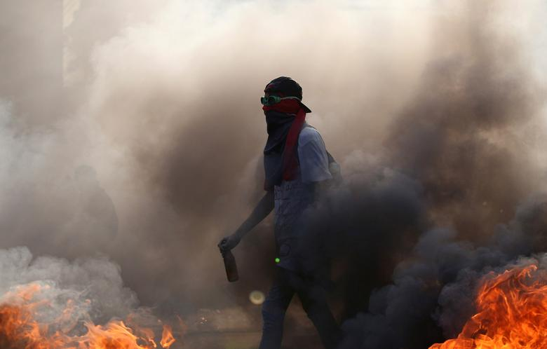 A demonstrator walks while building a fire on the street during a rally in Caracas, Venezuela, April 8, 2017. REUTERS/Carlos Garcia Rawlins