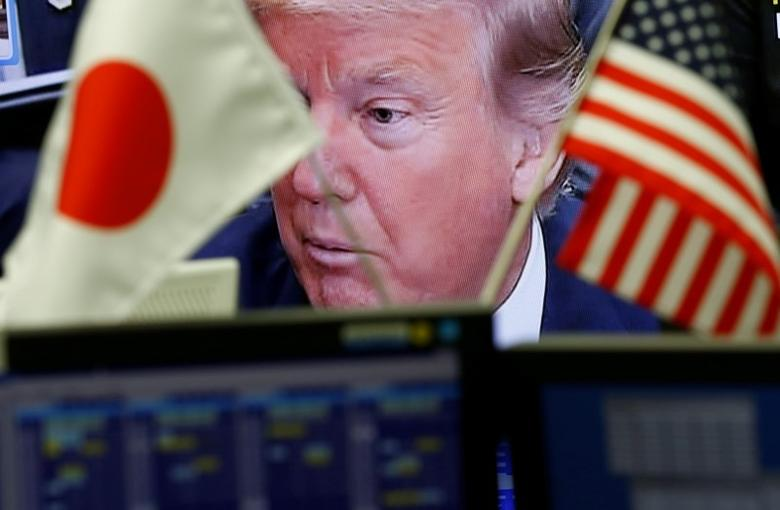 A TV monitor showing U.S. President Donald Trump is seen through national flags of the U.S. and Japan at a foreign exchange trading company in Tokyo, Japan February 1, 2017. Picture taken February 1, 2017.  REUTERS/Kim Kyung-Hoon