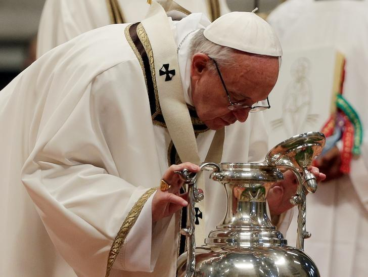 Pope Francis blows in an amphora to bless the oil of the Catechumens and the oil of the Sick as he leads the Chrism Mass at the Vatican, April 13, 2017. REUTERS/Max Rossi