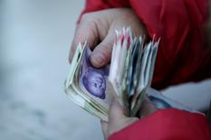Una mujer cuenta billetes de yuan en Pekín, China. 11 de febrero 2017.Los bancos chinos ofrecieron menos préstamos en marzo que el mes anterior, luego de que el Gobierno trató de contener los riesgos de una acumulación explosiva de deuda y un mercado de la vivienda sobrecalentado. REUTERS/Jason Lee