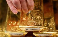 Imagen de archivo de un empleado del Banco Central alemán aplicando ultrasonido a un lingote de oro durante una rueda de prensa en Fráncfort, ene 16, 2013. El oro tenía una leve baja el viernes pero cerraría la semana en sus mejores precios desde junio tras alcanzar un máximo de cinco meses en la víspera, ya que los conflictos en torno a Corea del Norte y en Oriente Medio afectaban al dólar y hacían a los inversores buscar seguridad en el lingote.   REUTERS/Lisi Niesner/File Photo