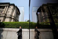 En la imagen, un peatón camina delante del edificio del Banco de Japón en Tokio, 22 de mayo de 2013. Se espera que en su informe de este mes el Banco de Japón ofrezca una visión de la economía más optimista que la de marzo, dijeron fuentes conocedoras del proceso, ya que las robustas exportaciones y la producción de las fábricas respaldan la recuperación en la tercera economía mundial. REUTERS/Yuya Shino/File Photo