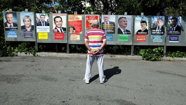 A man looks at campaign posters of the 11th candidates who are running in the 2017 French presidential election ,in Saint Andre de La Roche, near Nice, France, April 10, 2017. L-R : Nicolas Dupont-Aignan, Debout La France group candidate, Marine Le Pen, French National Front (FN) political party leader, Emmanuel Macron, head of the political movement En Marche ! (Onwards !), French Socialist party candidate Benoit Hamon, Nathalie Arthaud, France's extreme-left Lutte Ouvriere political party (LO) leader, Philippe Poutou, Anti-Capitalist Party (NPA) presidential candidate, Jacques Cheminade, ''Solidarite et Progres'' (Solidarity and Progress) party candidate, lawmaker and independent candidate  Jean Lassalle, Jean-Luc Melenchon, candidate of the French far-left Parti de Gauche, Francois Asselineau, UPR candidate, and Francois Fillon, the Republicans political party candidate.  REUTERS/Eric Gaillard/Files