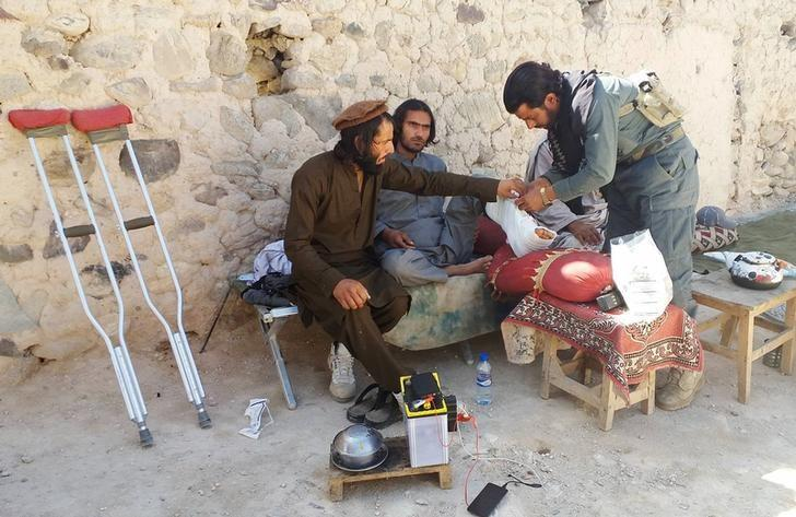 An Afghan police medic treats an injured policeman who was wounded in a military operation against suspected Islamic State militants in Achin district of Nangarhar province, in eastern Afghanistan, April 14, 2017. REUTERS/Parwiz
