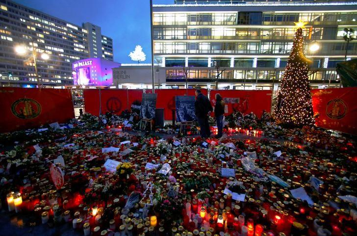 Flowers and candles are placed at the former Christmas market at Breitscheid square in Berlin, Germany, January 3, 2017, following an attack by a truck in December which ploughed through a crowd at the market.  REUTERS/Hannibal Hanschke/Files