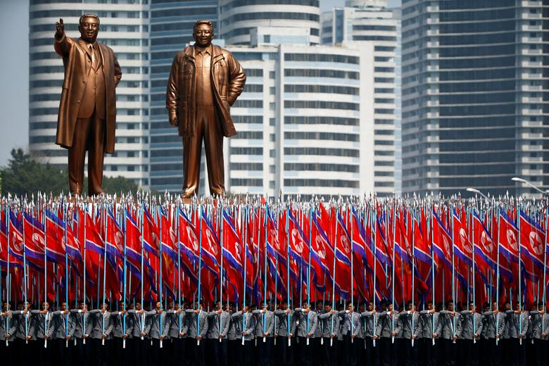 People carry flags in front of statues of North Korea founder Kim Il Sung (L) and late leader Kim Jong Il during a military parade marking the 105th birth anniversary Kim Il Sung, in Pyongyang April 15, 2017.  REUTERS/Damir Sagolj