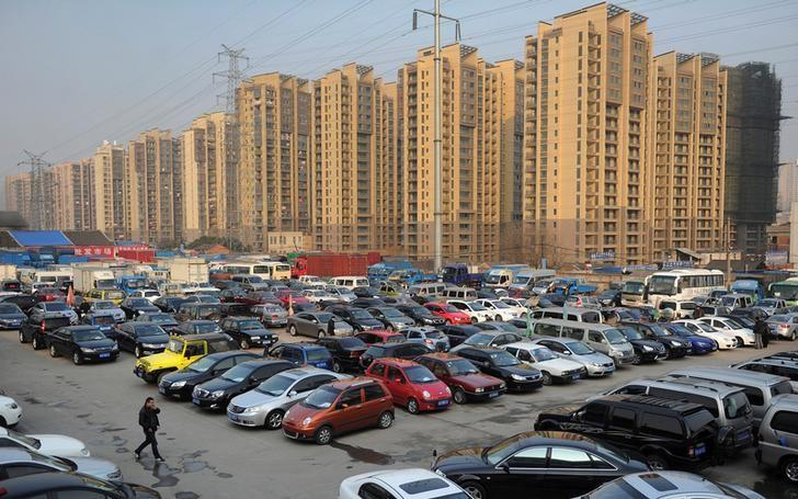 Car dealers and customers walk at a second-hand car market near a newly-built residential area in Hefei, Anhui province, China January 26, 2013.   REUTERS/Stringer/File Photo