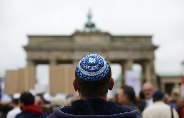A man wearing a kippah waits for the start of an anti-Semitism demo at Berlin's Brandenburg Gate September 14, 2014. Placard reads ' Never again'. REUTERS/Thomas Peter