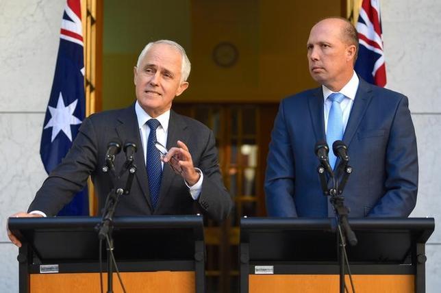 4月18日、オーストラリアのターンブル首相(左)は、外国人に人気の「457」一時就労ビザ(査証)を廃止し、より高度な英語力や労働スキルを必要とするビザに置き換える方針を明らかにした。写真はダットン移民大臣と記者会見に参加する同首相。キャンベラの議事堂で撮影(2017年 ロイター)