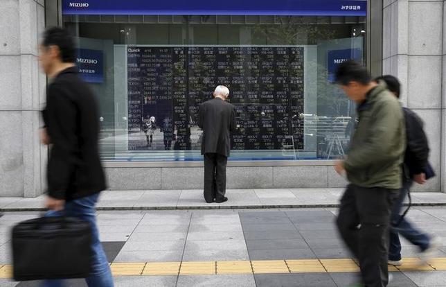 4月19日、寄り付きの東京株式市場で、日経平均株価は前日比91円26銭安の1万8327円33銭となり、反落して始まった。写真は株価ボードを眺める男性、都内で昨年4月撮影(2017年 ロイター/Toru Hanai)