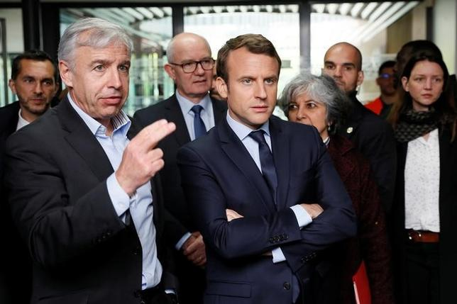 Emmanuel Macron, head of the political movement En Marche !, or Onwards !, and candidate for the 2017 French presidential election, listens to General Director of the optic group KRYS Jean-Pierre Champion (L) during his visit at the headquarters of the KRYS group in Bazainville, France, April 18, 2017.  REUTERS/Thomas Samson/Pool
