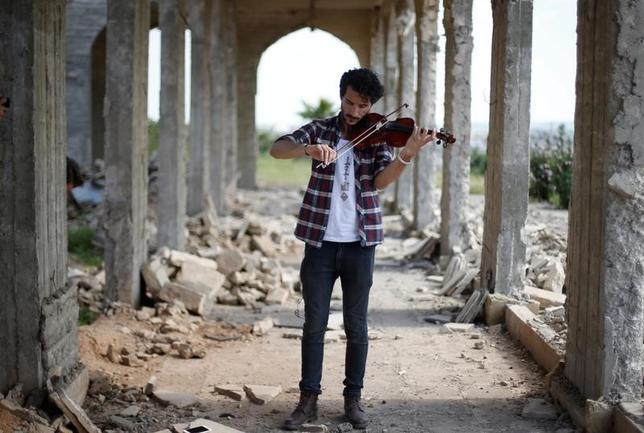 4月19日、過激派組織イスラム国(IS)に自宅を襲撃され楽器を押収されたこともあるイラク人男性バイオリニストAmeen Mukdadさん(28)が19日、依然としてISが勢力を保ち音楽や娯楽活動を禁止しているモスルで、1時間にわたるコンサートを行った(2017年 ロイター/ Muhammad Hamed )