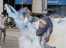 Manifestante de oposição arremessa de volta granada de gás lacrimogêneo lançada pela polícia durante protesto. 19/04/2017 REUTERS/Marco Bello