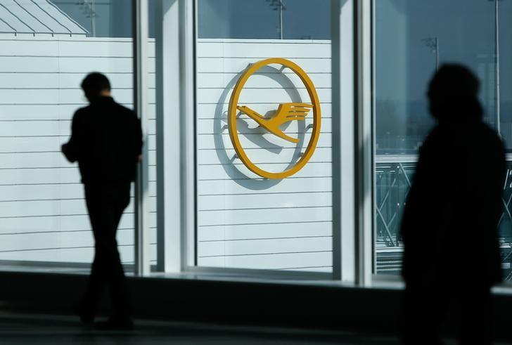 Traveller walk past a sign of German airline Lufthansa before the company's annual news conference at the airport in Munich, Germany, March 16, 2017. REUTERS/Michaela Rehle