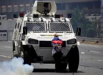 Una manifestante opositora bloque al paso a un vehículo de la policía antidisturbios durante una protesta contra el presidente de Venezuela, Nicolás Maduro, en Caracas. 19 de abril. REUTERS/Marco Bello