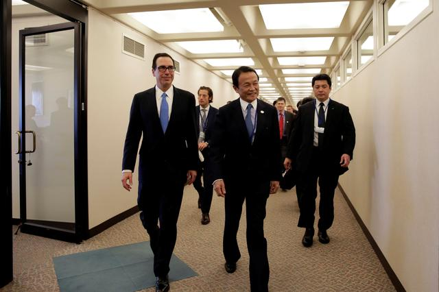 U.S. Treasury Secretary Steven Mnuchin (L) and Japanese Finance Minister Taro Aso walk after their meeting during the IMF/World Bank spring meetings in Washington, U.S., April 20, 2017. REUTERS/Yuri Gripas