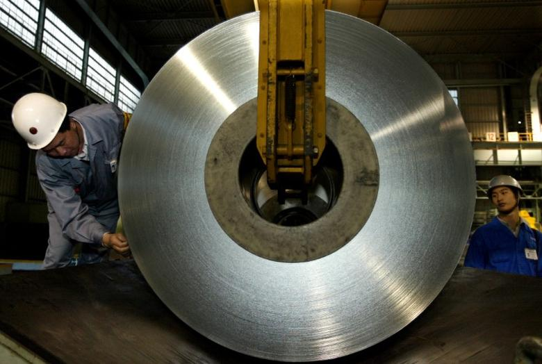 Chinese workers unload a roll of tin plate at a plant on the outskirts of Shanghai November 20, 2003. REUTERS/Claro Cortes/File Photo