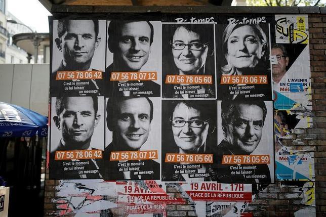 4月20日、フランス大統領選の第1回投票では、異端の経済政策を掲げる2人が票の5分の2以上を獲得する可能性がある。写真は候補者のポスター。パリで19日撮影(2017年 ロイター/Benoit Tessier)