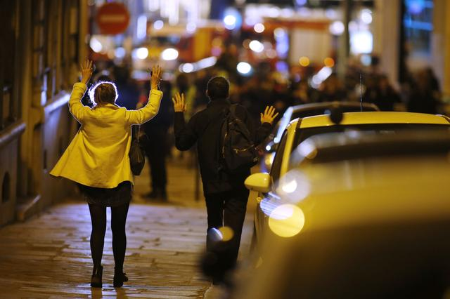 People raise their arms to show their hands as they walk towards police on a side road near the Champs Elysees Avenue after a shooting incident in Paris, France, April 20, 2017. REUTERS/Benoit Tessier