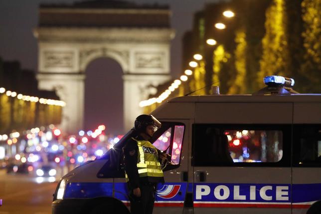 4月21日、フランスのパリ中心部にあるシャンゼリゼ通りで20日夜、警官1人が死亡、2人が負傷した銃撃事件で、内務省は21日、警察当局が事件に関連した疑いで2人目の容疑者の行方を追っていると明らかにした。写真は事件現場で警戒にあたる警察官。20日撮影(2017年 ロイター/CHRISTIAN HARTMANN)