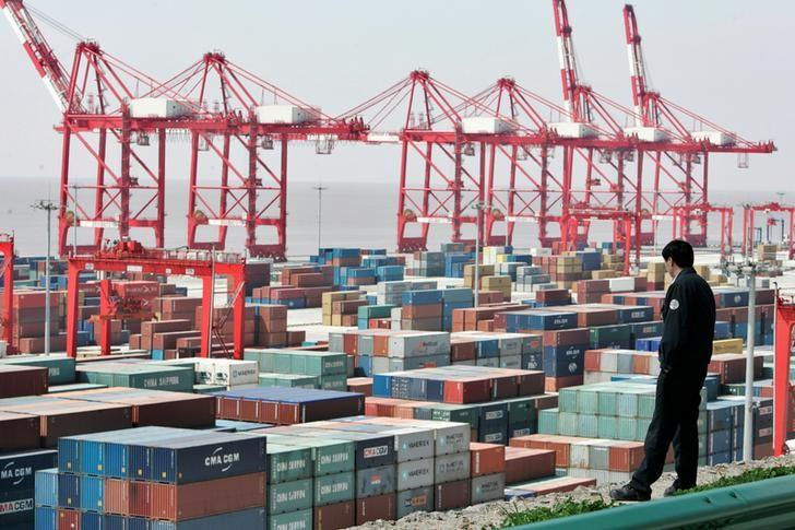 FILE PHOTO: A man watches containers at the Yangshan deepwater port in Shanghai March 7, 2007.  REUTERS/Aly Song/File Photo