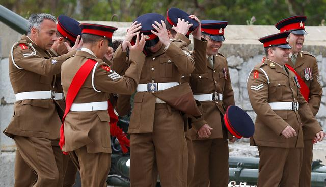 Members of the Royal Gibraltar Regiment hold onto their caps in the wind as they prepare to fire a 21 gun salute to mark the 91st birthday of Britain's Queen Elizabeth in the British overseas territory of Gibraltar, historically claimed by Spain, April 21, 2017. REUTERS/Phil Noble