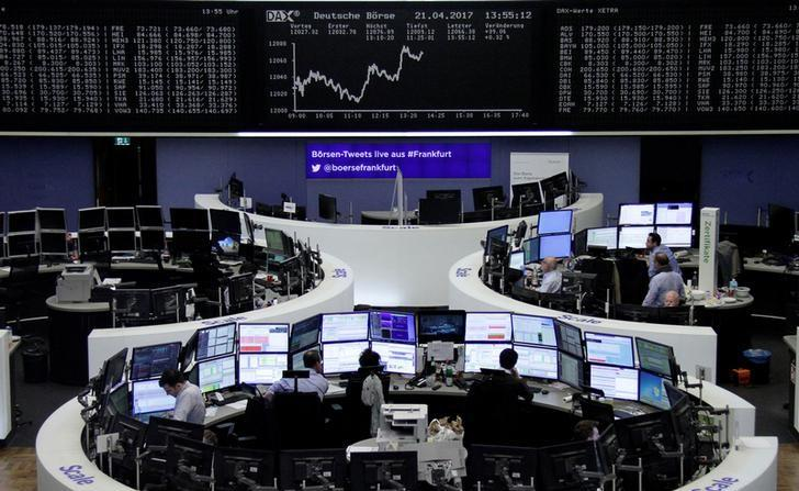 Traders work at their desks in front of the German share price index, DAX board, at the stock exchange in Frankfurt, Germany, April 21, 2017. REUTERS/Staff/Remote