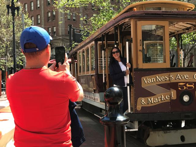 Tourists take pictures of an immobile cable car during a power cut in downtown San Francisco, California, U.S. April 21, 2017.  REUTERS/Alexandria Sage