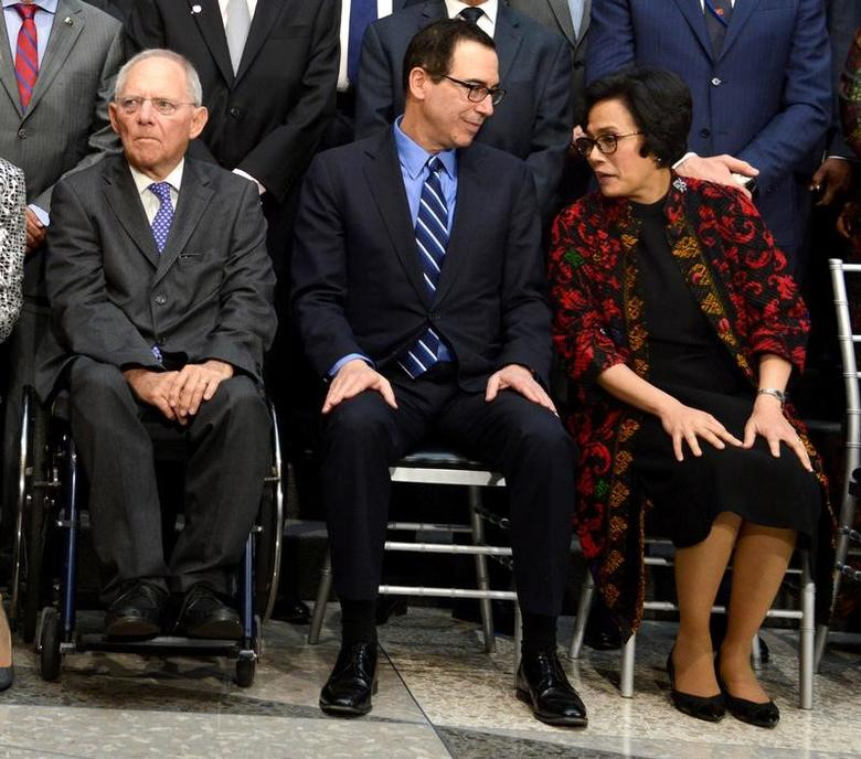 U.S. Treasury Secretary Steven Mnuchin (C) chats with Indonesia's Finance Minister Sri Mulyani Indrawati as German Finance Minister Wolfgang Schauble takes his seat for a ''family'' photo for the International Monetary and Financial Committee (IMFC), as part of the IMF and World Bank's 2017 Annual Spring Meetings, in Washington, U.S., April 22, 2017.   REUTERS/Mike Theiler