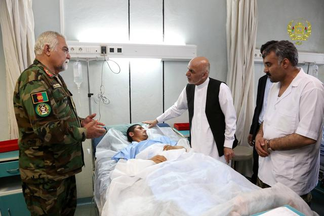 Afghanistan's President Ashraf Ghani visits a victim wounded in April 21's attack on an army headquarters, in Mazar-i-Sharif, northern Afghanistan April 22, 2017. Presidential Palace /Handout via REUTERS