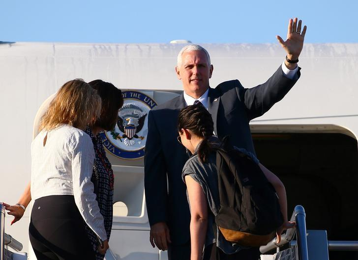 U.S. Vice President Mike Pence (top R) waves from the steps of Air Force One as his wife Karen (2nd L) and their daughters Charlotte (L) and Audrey step aboard to depart Sydney, Australia, April 24, 2017.    REUTERS/David Gray