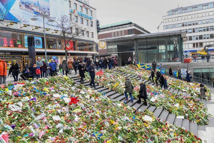 People lay flowers near the crime scene at Ahlens department store at the pedestrian street Drottninggatan in central Stockholm, Sweden, April 12, 2017. TT NEWS AGENCY/ Fredrik Sandberg via REUTERS