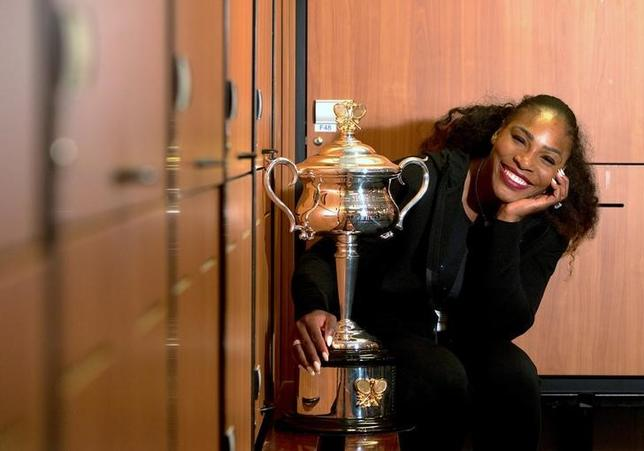 Serena Williams of the U.S. sits next to the trophy after winning the Women's singles final against sister Venus at the Australian Open tennis tournament in Melbourne, Australia in this handout image taken January 28, 2017. Fiona Hamilton/Courtesy of Tennis Australia/Handout via REUTERS/Files