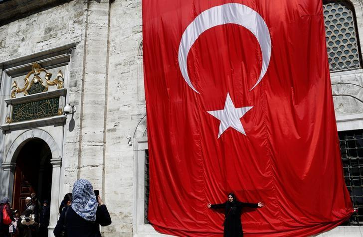 A woman poses in front of a huge Turkish flag in Istanbul, Turkey, April 13, 2017. REUTERS/Murad Sezer